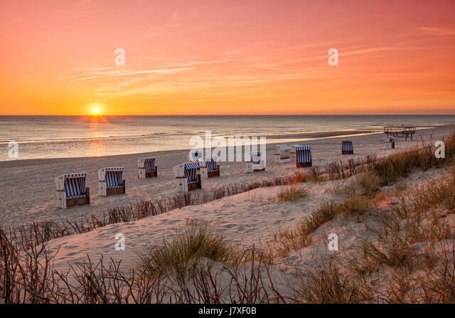 Beach chairs at North Sea beach of Hörnum, Sylt, in sunset - Stock Image