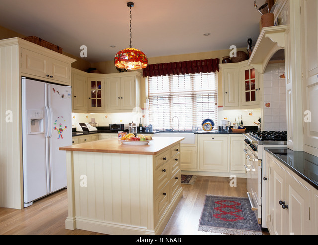 Cream island unit and fitted cupboards in country kitchen with large
