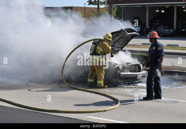 Genial Firefighter Putting Out Fire On Burning Mercedes Stock Image