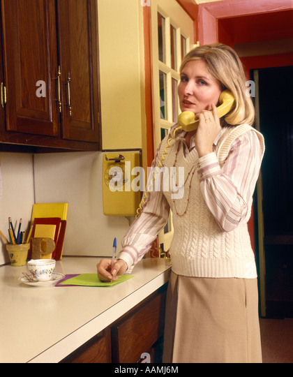 Amazing 1970 1970s WOMAN HOUSEWIFE TALKING ON YELLOW WALL PHONE IN KITCHEN NOTE PAD  ON COUNTER WRITING