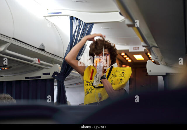 Flight attendant on airplane gives safety demonstration in airplane
