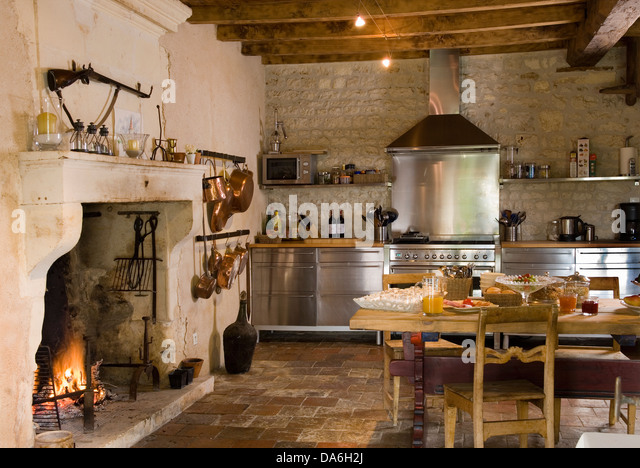 fireplace in kitchen. lit fire in fireplace country kitchen with rustic wooden table and chairs stainless steel fitted