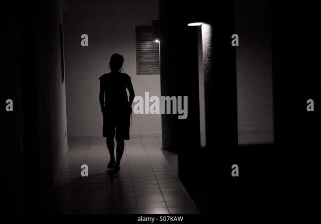 A Woman Walking Down A Dark Hallway In Dominican Republic   Stock Image
