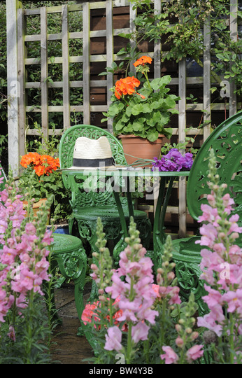 Summer Seating Area With Garden Furniture Potted Geraniums Antirrhinums And Panama Hat Norfolk