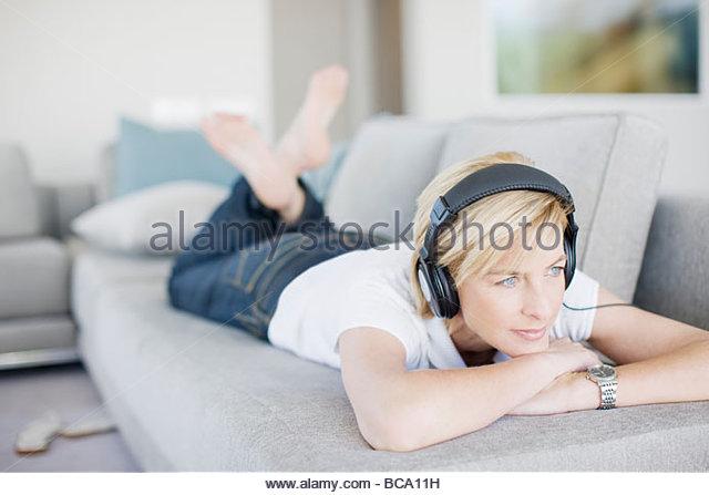 woman listening to headphones in living room stock image bca living room furniture
