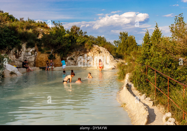 people relaxing in warm pools below the famous spa town of bagno vignoni in southern tuscany
