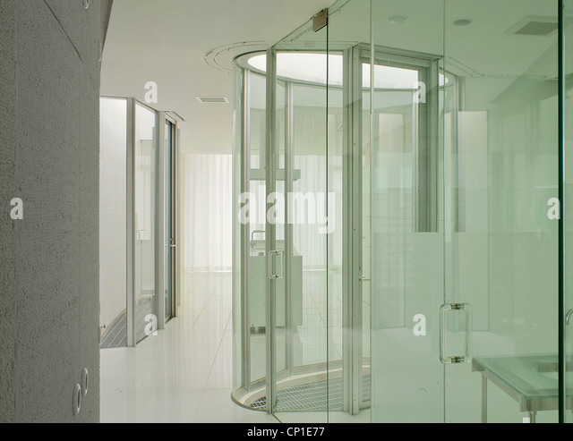 shower unit enclosed in glass cubicle in bathroom stock image