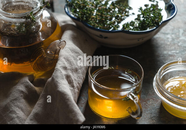 Kettle with green tea, thyme and honey on the table closeup horizontal - Stock Image