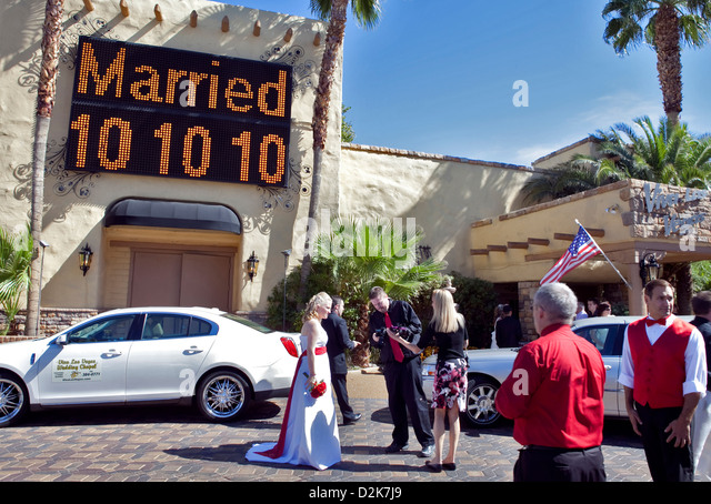 A RECENTLY MARRIED COUPLE OUTSIDE VIVA LAS VEGAS WEDDING CHAPEL IN DOWNTOWN OCTOBER
