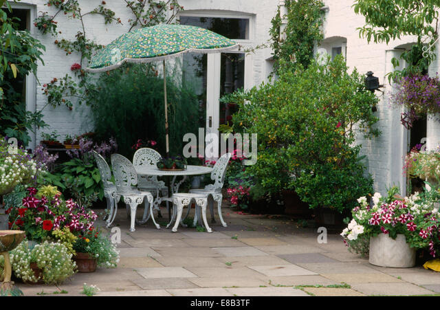 Green umbrella above white wrought iron table and chairs on patio stock photo picture and - Care geraniums flourishing balcony porch ...