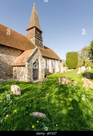 Thame, England, UK - April 18, 2015: Spring sunshine on the church, spire and graveyard of St Mary's Church - Stock Image
