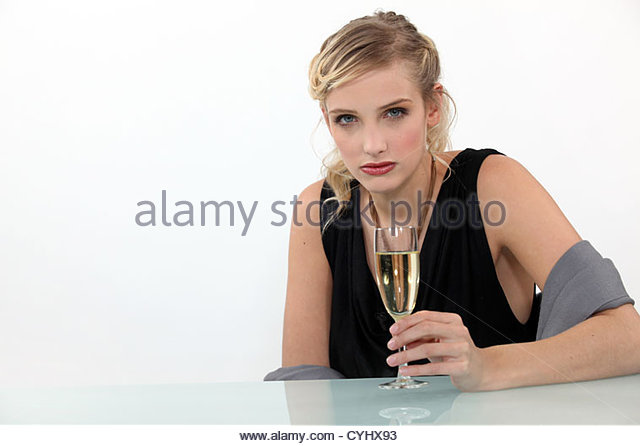 Crying woman drinking a glass of champagne - Stock Image