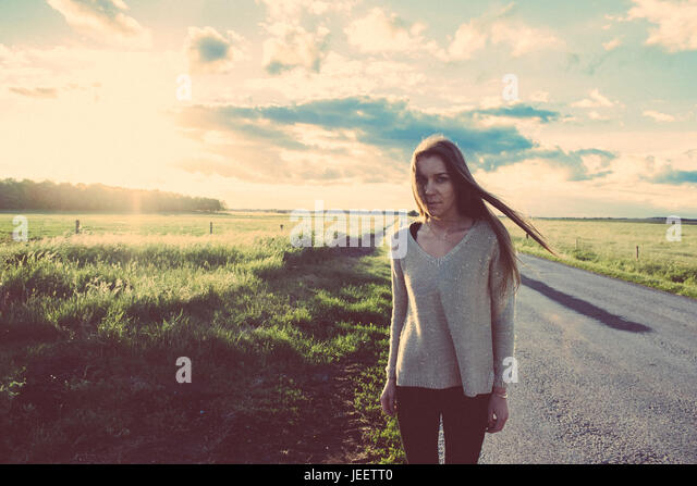 Film photo of woman on the road in summer sunset - Stock Image