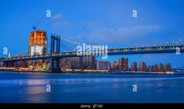 Brooklyn Bridge and NYC Skylinet night with reflection of  the skyline on East River - Stock Image
