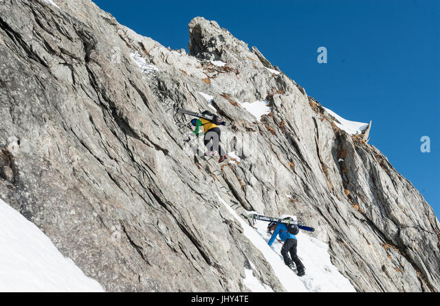Ski tour in the mountains of the Disentis region in Switzerland. The skis are mounted on the backpacks for the climb - Stock Image