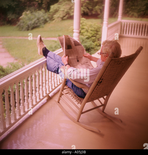 Mature White Hair Man Sitting On A Rocking Chair On The Front Porch Reading  The Newspaper