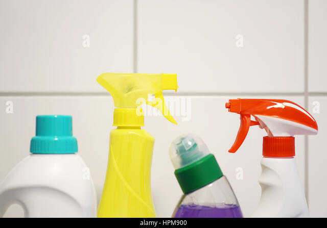various cleaning products and detergent in front of white bathroom tiles with copy space stock