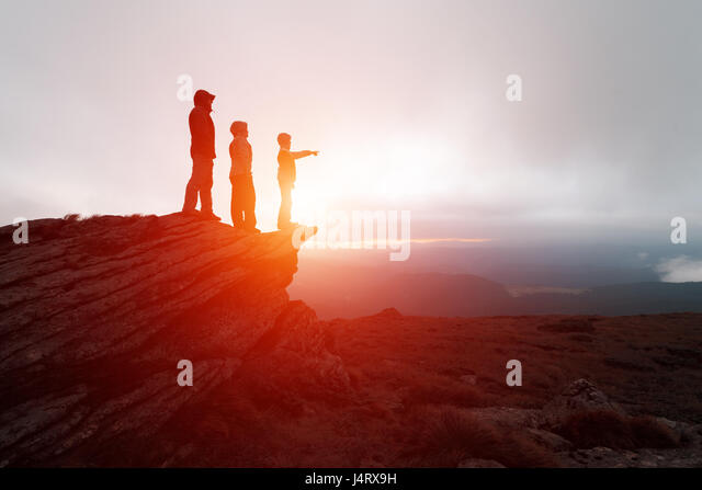 Family of tourists staying on the edge of the cliff against the backdrop of an incredible mountain landscape. Evening - Stock Image