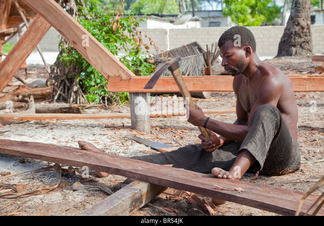 carpenters adze. nungwi, zanzibar, tanzania. dhow construction, boat building. carpenter using an adze carpenters