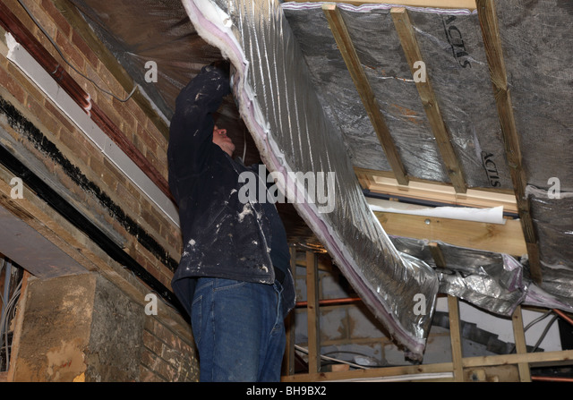 Installation Of Foil Roof Insulation In A Domestic Property   Stock Image