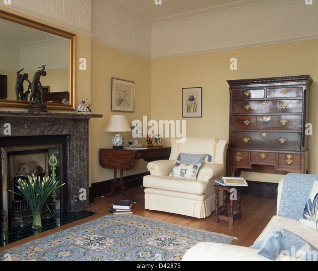 Antique Oak Chest On And Cream Armchair In Living Room With Mirror Above