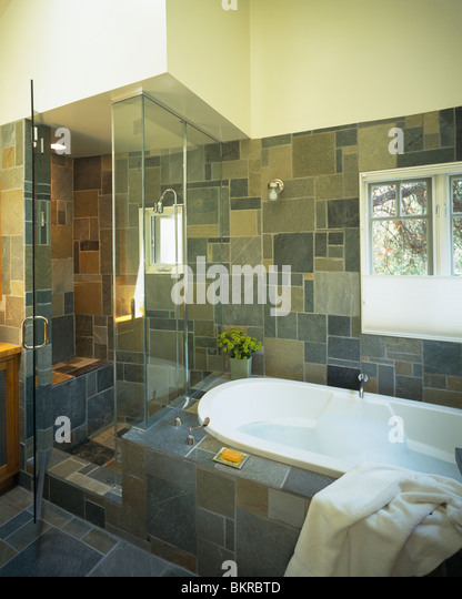 glass shower cabinet beside bath in modern slate tiled bathroom