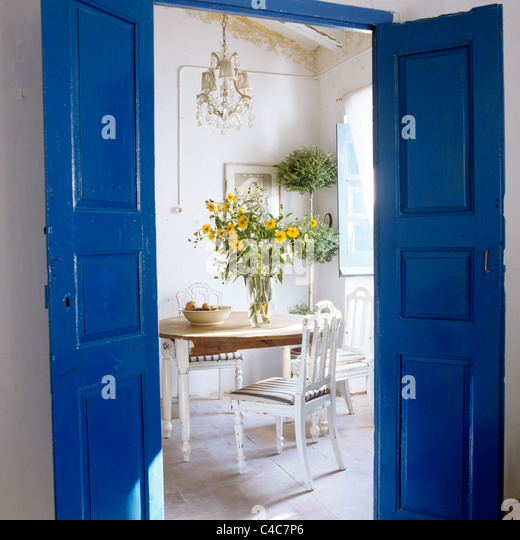 View Through Blue Painted Double Doors Into White Dining Room