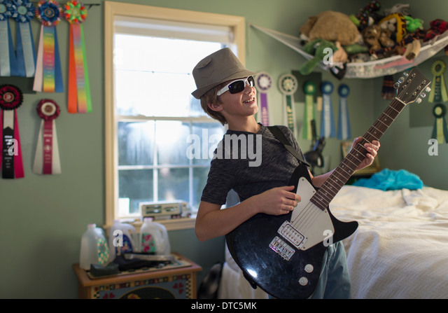 Boy playing guitar in bedroom   Stock Image. Boy Playing Guitar In Bedroom Stock Photos   Boy Playing Guitar In