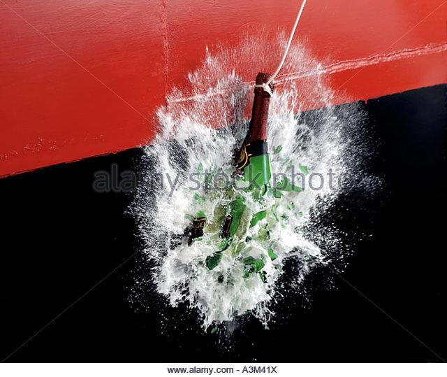 BOTTLE OF CHAMPAGNE SMASHING AGAINST RED SHIP HULL - Stock Image