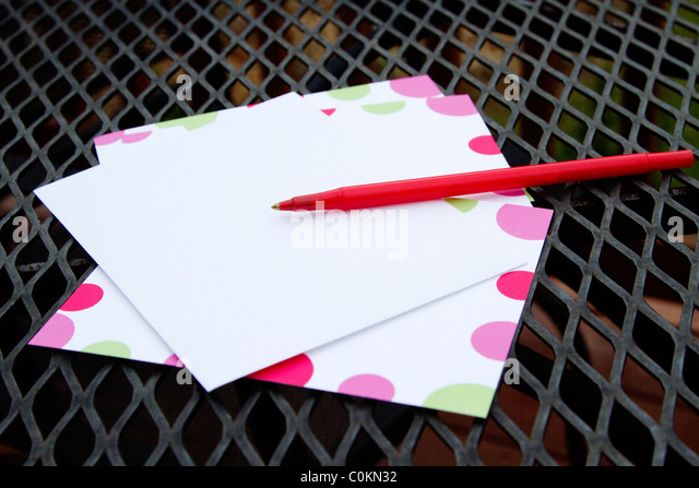Red Pen And Note Paper Placed On Black Wrought Iron Patio Table Top With  Deck Fencing