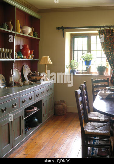 Large Gray Painted Dresser In Country Dining Room With Polished Wooden Floorboards