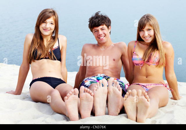 Young People Sitting On Sand And Tanning A Sunny Summer Day