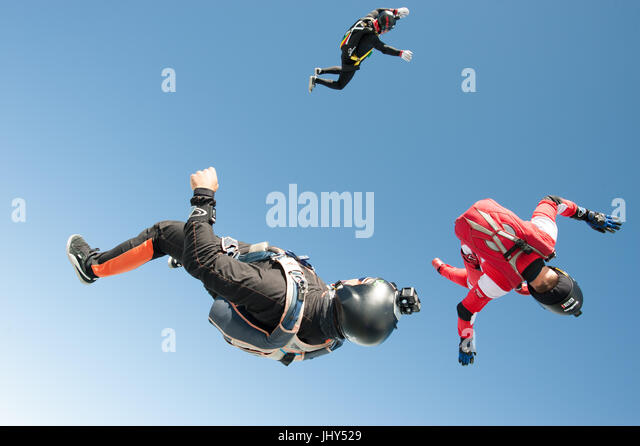 Three skydivers tumbling through the air after exitig the airplane - Stock Image