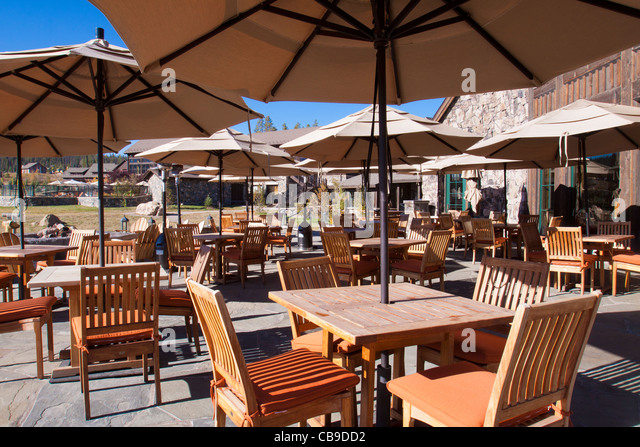 Outdoor Patio Dining At A Mountain Resort Lodge With Umbrellas Over Wood  Tables And Chairs