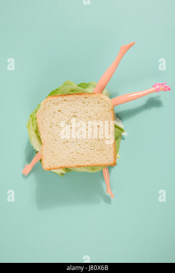 Parts of a doll's body in a sandwich with salad and soft bread on a minimal background color. pop fun and quirky - Stock Image