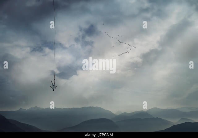Young man falling from the sky with a rope tied to his leg as safety insurance. Base jump, mysterious crash, life - Stock Image