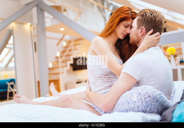 Romantic couple in love lying on bed and being passionate   Stock Image. Couple Bedroom Love Romance Kiss Intimacy Bed Stock Photos