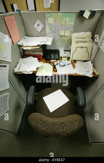 messy cubicle in highrise office building stock image