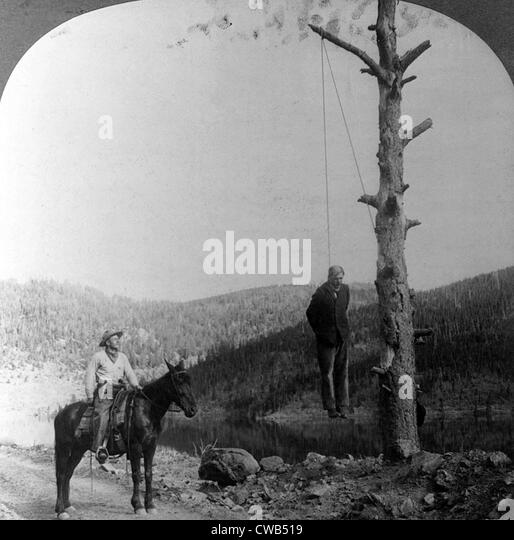 Wild west sheriff on horseback looking at stage coach robber hanging
