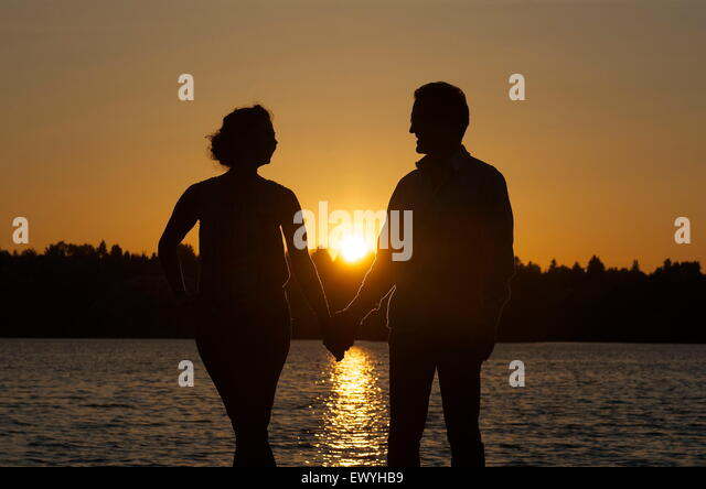 silhouette of a couple holding hands stock image