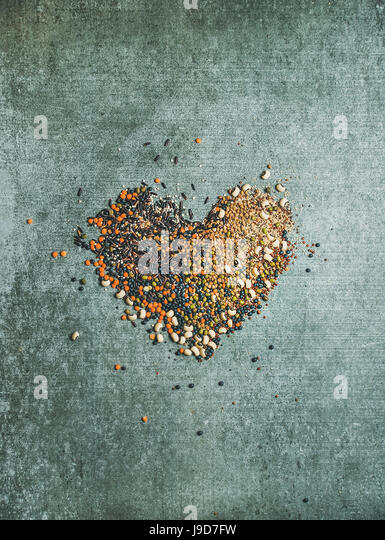 Variety of raw grains, beans, cereals in shape of heart - Stock Image