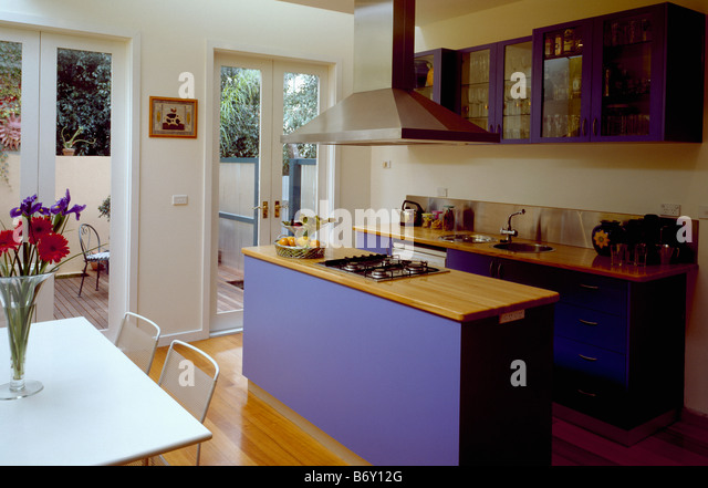 Wooden worktop on blue island unit in modern openplan for G plan dining room unit