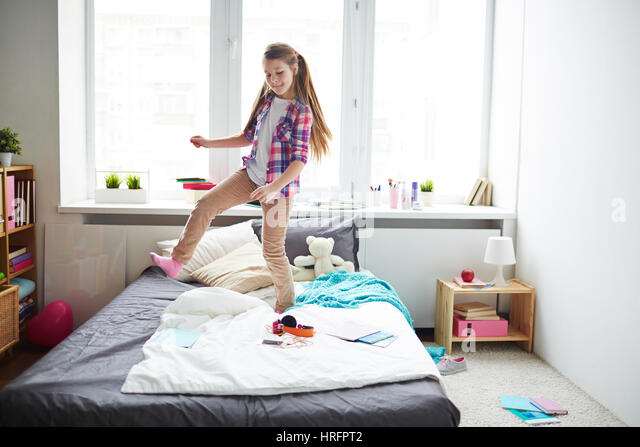 Long haired pretty school girl jumping and dancing on bed in her modern  comfortable room. Girl Dancing Bedroom Stock Photos   Girl Dancing Bedroom Stock
