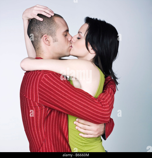 one young couple hugging kissing on studio isolated gray background   Stock  Image. Young Couple Lovers Kissing On Stock Photos   Young Couple Lovers