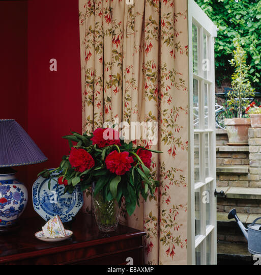 Red Peonies In Vase On Table Beside French Window With Floral Curtains Country Dining Room