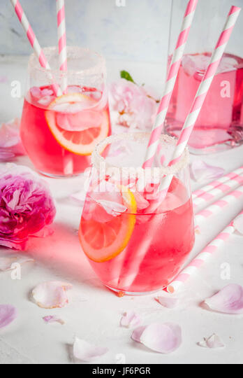 Summer refreshment drinks. Light pink rose cocktail, with rose wine, tea rose petals, lemon. On a white stone concrete - Stock Image