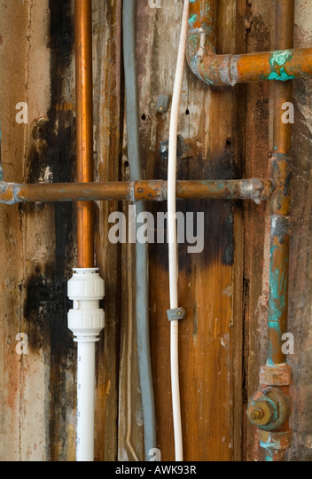 Close Up View Of A Plumbing Joint Between Copper And Plastic Piping In A Boiler Cupboard