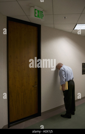 worker puts head against hallway wall in office worker to relieve stress stock image business nap office relieve