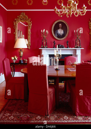 Red Loose Covers On Chairs At Oval Antique Table In Bright Red Dining Room  With Brass