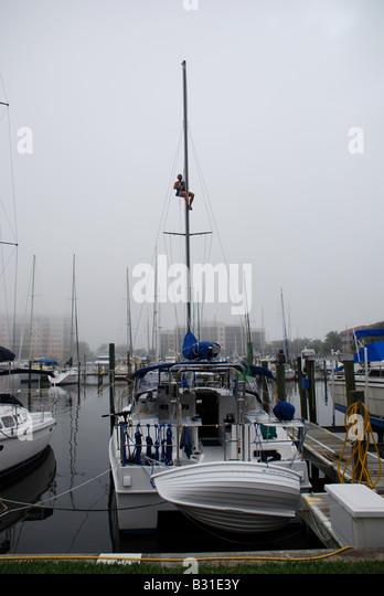 bosun chair sailboat. woman using a bosun s chair to climb the mast of 36 catamaran make sailboat k